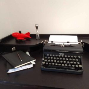 black royal typewriter on brown-black wooden desk desk with notebooks, fountainpen, and two small desk ornaments (red airplane and silver cat)