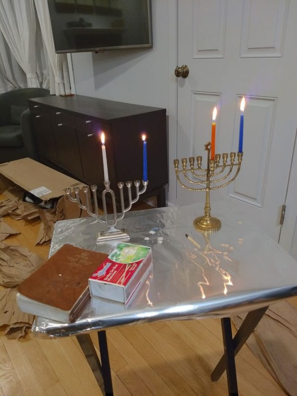 two menorahs on aluminum foil table with first candle of each lit.