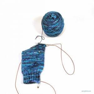 Cake of sock yarn and a sock in progress, cuff-down, magic loop.