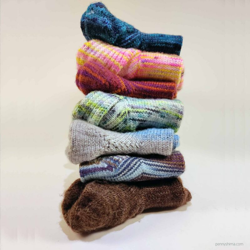 stack tower of 7 pairs of handknit socks in a variety of mostly bright colors