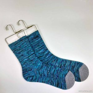 pair of handknit socks, in varigated blues with grey toes. shown laid flat on metal sock blockers
